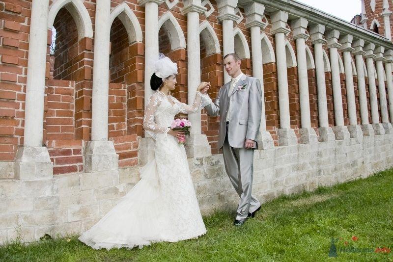 Жених и невеста, взявшись за руки,  стоят на фоне кирпичной стены - фото 61962 мадамка