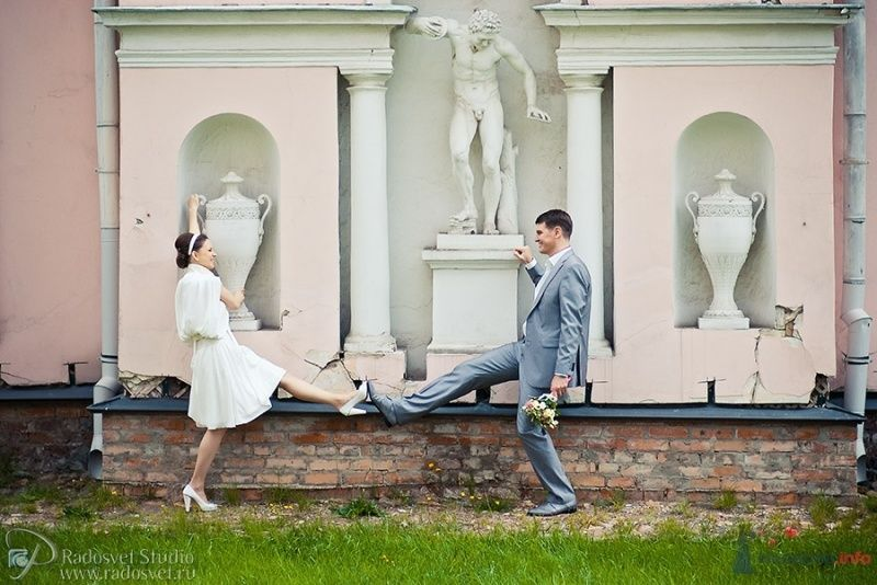 Жених и невеста стоят с поднятой ногой позле белой стены