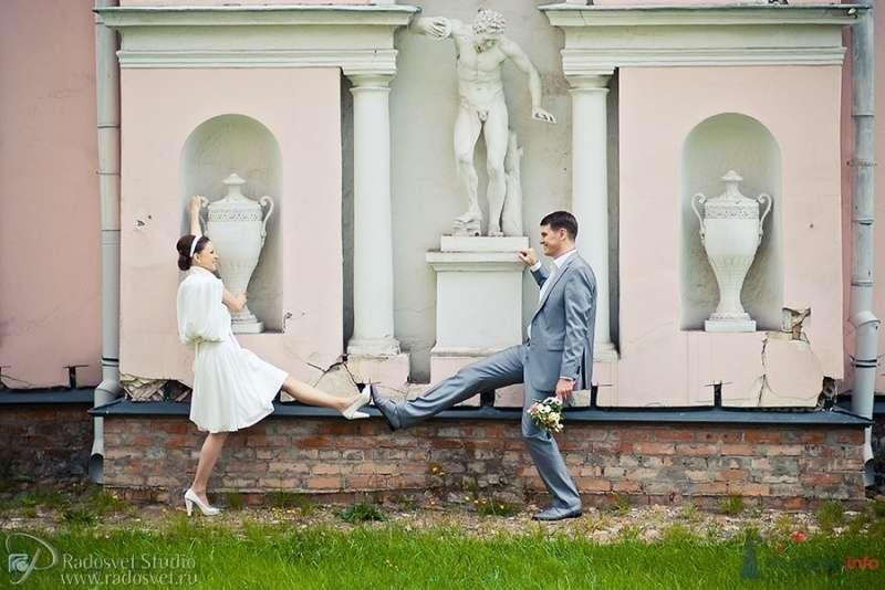 Жених и невеста стоят с поднятой ногой позле белой стены - фото 55730 Фотограф Радосвет Лапин