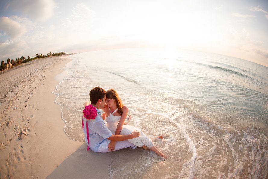 На берегу моря, волна омывает жениха с невестой, они сидят на песке обнимая друг друга в белых нарядах - фото 2120960 Чунгуров Илья - фотограф
