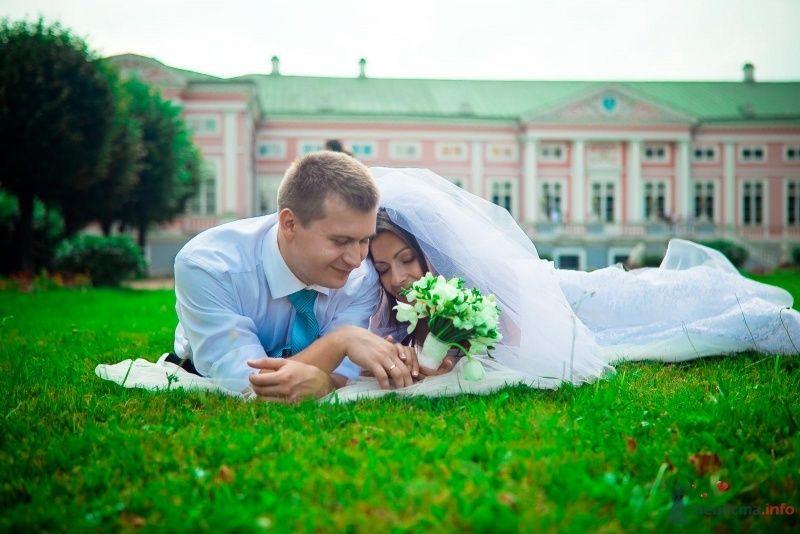 Жених и невеста лежат, прислонившись друг к другу, на траве - фото 54374 Anjuta