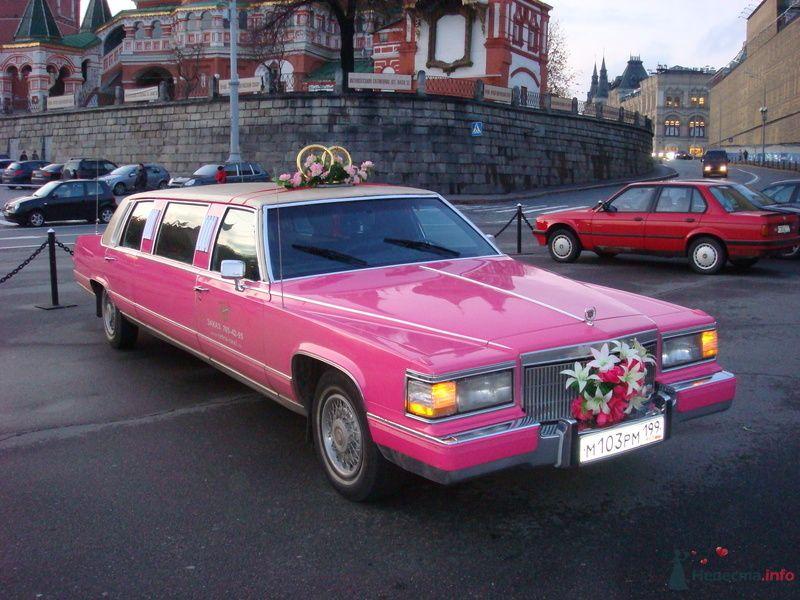 Малиновый Лимузин, украшенный  стойкой из колец, на фоне храма. - фото 74928 Ретро-такси - аренда лимузина