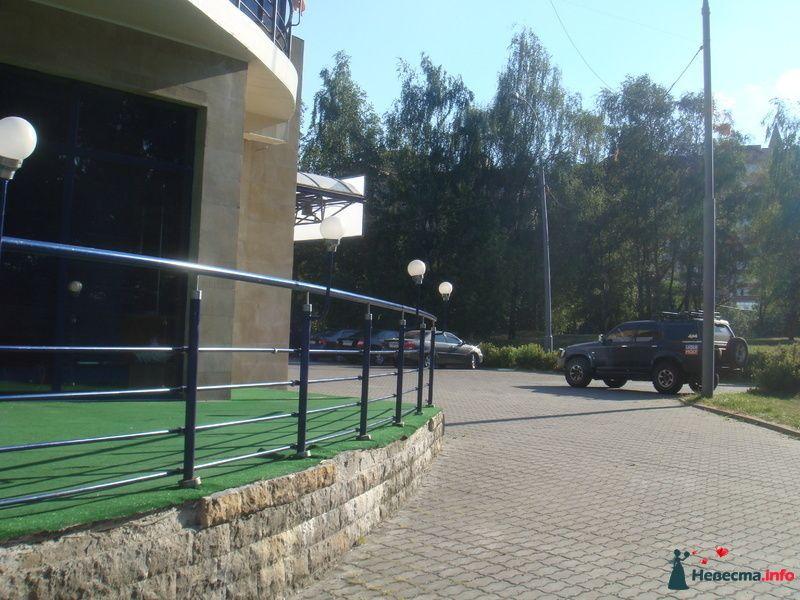 Вид на парковку, где припаркуются машины и лимузин.