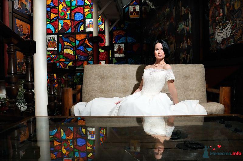 Невеста в белом длинном платье сидит на сером диване в комнате - фото 105912 Фотограф Хасан Йенер