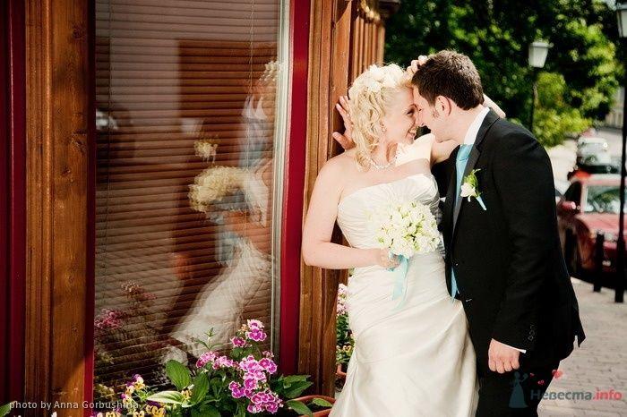 Жених и невеста стоят, прислонившись друг к другу, возле домика - фото 56313 Анна Горбушина - фотоагентство SunStudio