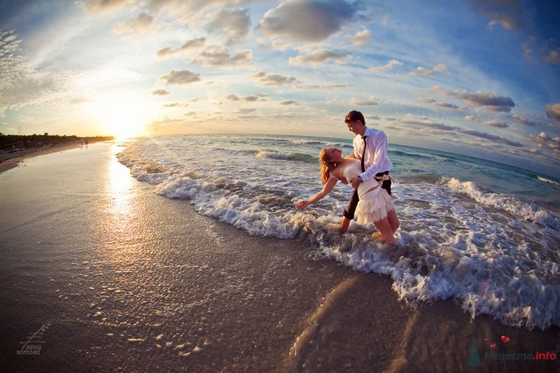 Жених и невеста, прислонившись друг к другу, стоят на фоне моря и