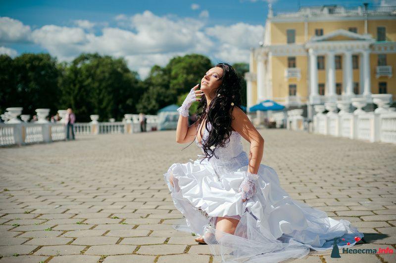 Невеста в белом платье сидит в парке на фоне большого здания - фото 89217 Любовь Ю.