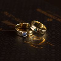 Обручальные кольца с православной молитвой. Обручальные кольца из золота 750 пробы, с православной молитвой, нанесённой внутри и снаружи колец. Мужское кольцо украшает большой цейлонский сапфир, весом чуть менее карата, в женском кольце натуральный голубо