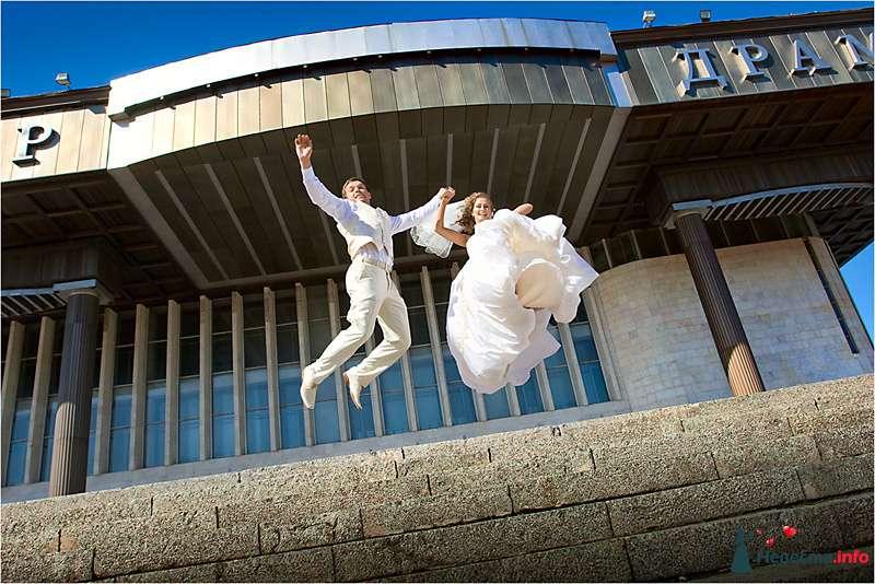Жених и невеста, взявшись за руки,  подпрыгнули в воздухе на фоне серого здания - фото 90839 LevBodrov