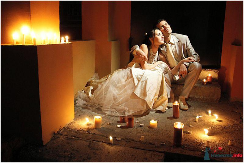 Жених и невеста сидят, прислонившись друг к другу, на полу со свечами - фото 90840 LevBodrov
