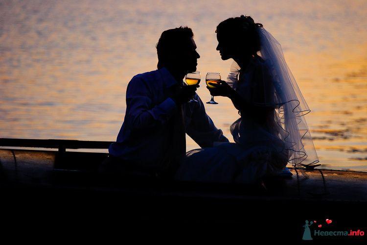 Жених и невеста сидят на берегу озера с бокалами в руках - фото 90845 LevBodrov