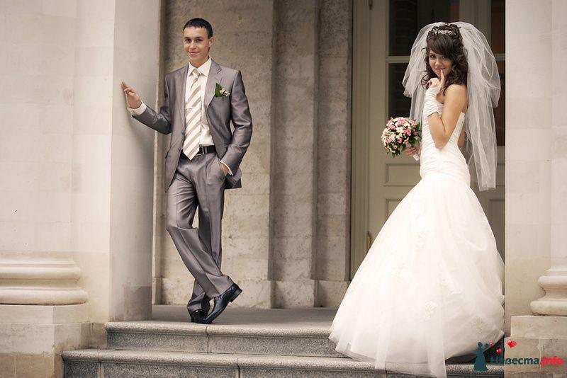 Жених и невеста стоят возле серого здания - фото 92529 Ведущая - Ольга Павликова