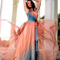 Среди белых колонн, подняв руки, стоит подружка невесты в длинном развивающемся платье с многослойным асимметричным низом и приталенным открытым лифом из оранжево-голубой спектральной ткани.