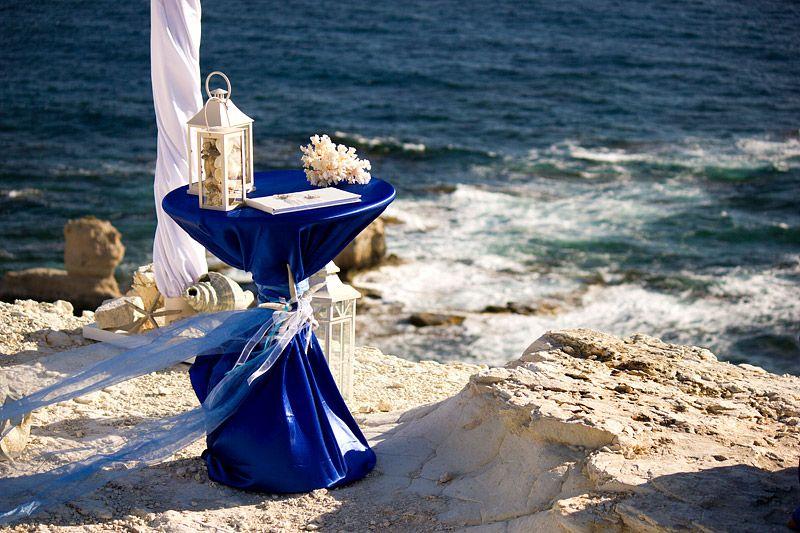 На берегу моря стоит столик, накрыт синей тканью,возле арки, для церемонии молодых - фото 2492553 Агентство Гименей - организация свадеб на Кипре