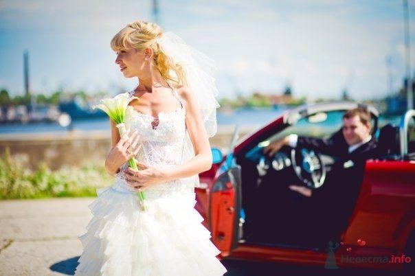 Невеста в белом длинном платье стоит возле красной машины - фото 59067 Mukha