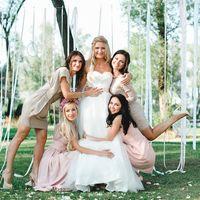 """Невесту в белом открытом длинном платье """"принцесса"""" обнимают подружки в коротких бежевых и розовых платьях под деревом декорированным белыми длинными лентами"""