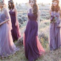 Подружки в веночках из цветов сиреневых оттенков, многослойных длинных открытых приталенных платьях из прозрачной ткани фиолетового и сиреневого оттенков с букетом цветов идут по полю