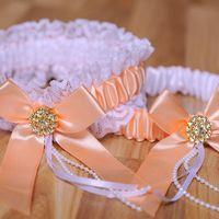 Подвязочки в бело-персиковых тонах с украшениями золотого цвета на бантах