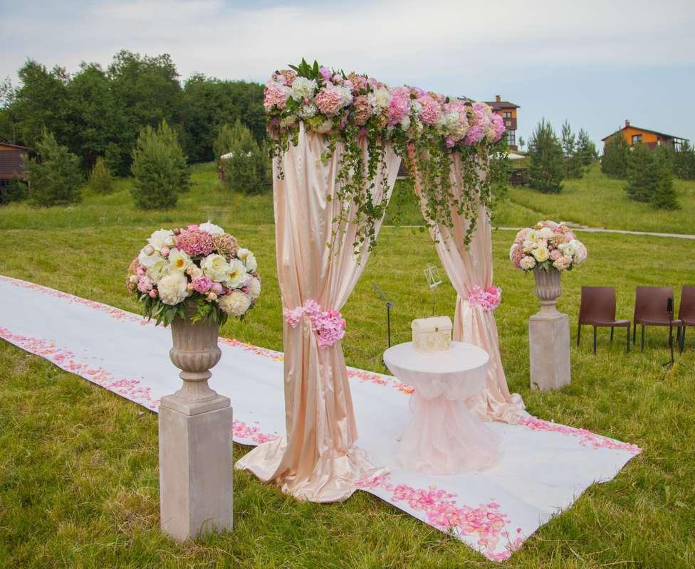 Квадратная арка с композицией из живых цветов, задрапированная бежевой тканью и розовыми лентами, на фоне тумб с вазами в цветах - фото 2580447 Premiumflor - декор и флористика