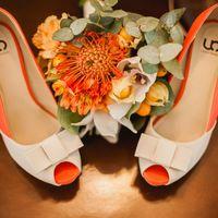 Открытые туфли невесты оранжево-белого цвета и вегетативный свадебный букет  на светло-коричневом  линолиуме