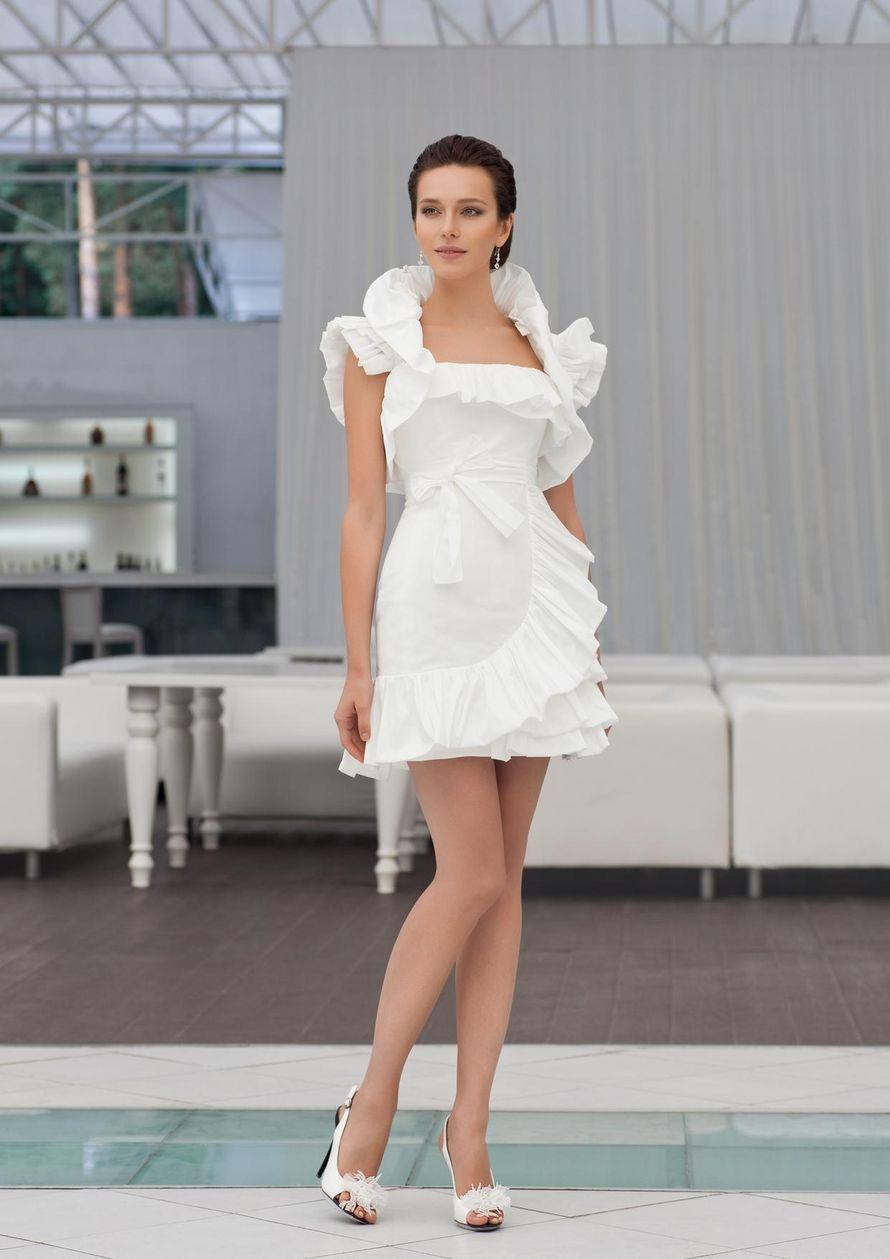 """Poline: коротенькое и безумно женственное платье, дополненное легкомысленными рюшечками. При этом платье имеет плотный корсет и плавную линию декольте, что позволяет ему идеально подчеркивать достоинства любой фигуры. Цвет платья: белый, молочный, кремов - фото 1712039 Свадебный салон """"Art Podium"""""""