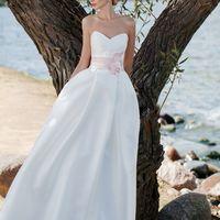 Love Настоящая любовь не требует слов! Лаконичное платье А-силуэта, с мягкими складками и плавной сердцевидной линией декольте. Широкий пояс с крупным цветком. И конечно, так полюбившийся невестам, красивый бант сзади. Платье имеет недлинный, удобный шлей