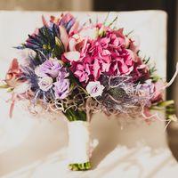 0ригинальный букет невесты из ярко-розовых гортензий, розовых орхидей, сиреневых эустом, голубых эрингиумов, декорированный белой лентой и декоративными элементами