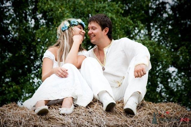 Жених и невеста сидят, прислонившись друг к другу, на стоге сена