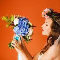 Образ невесты в английском стиле с венком на голове и букетом невесты из голубых гортензий, белых гвоздик, розовых роз и зелени в руках