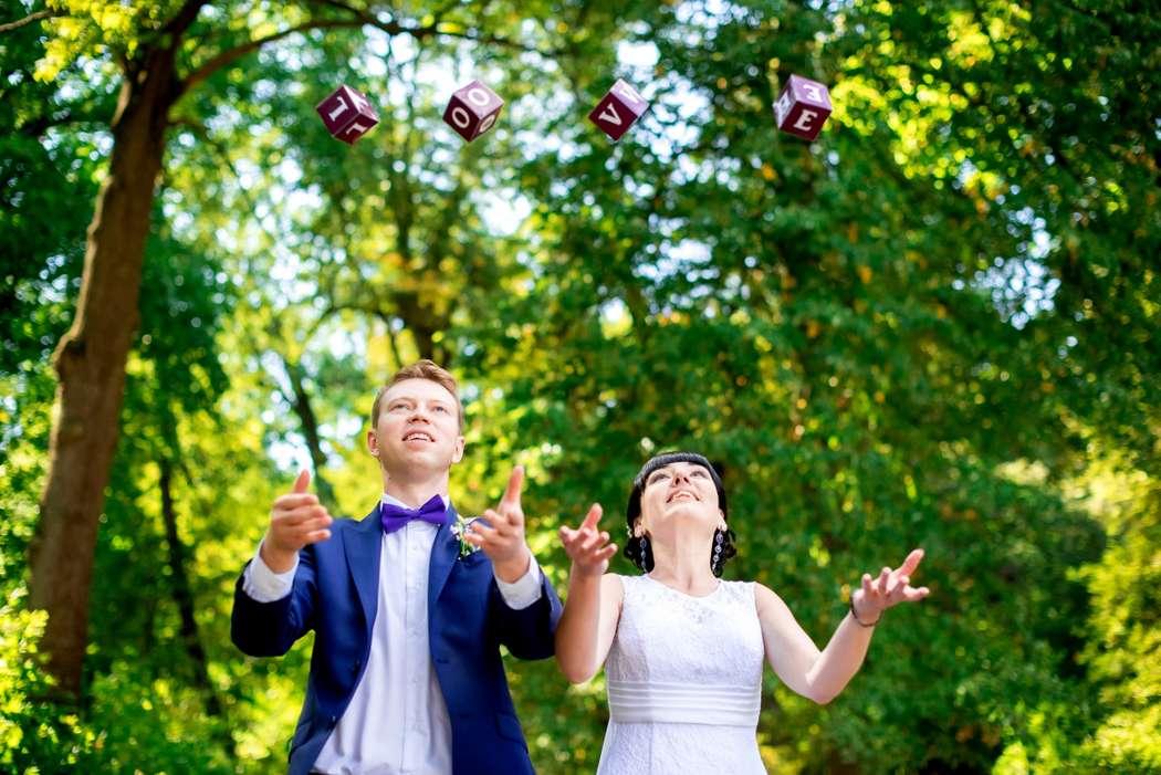 Жених и невеста подбрасывают вверх кубики на фоне зеленых деревьев - фото 3564847 Фотограф Юлия Старкова