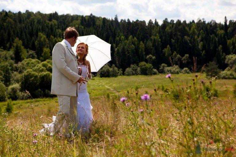 Жених и невеста стоят, прислонившись друг к другу, на фоне леса