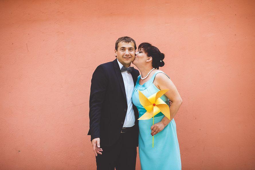 На фоне розовой стены с жёлтым ветряком в руках девушка целует парня - фото 2089196 Свадебный фотограф Александр Сарибекян