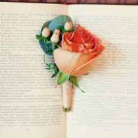 Бутоньерка из оранжевой розы и белых ягод ранункулюса и  зеленых листьев котинуса, декорированная оранжевой атласной лентой