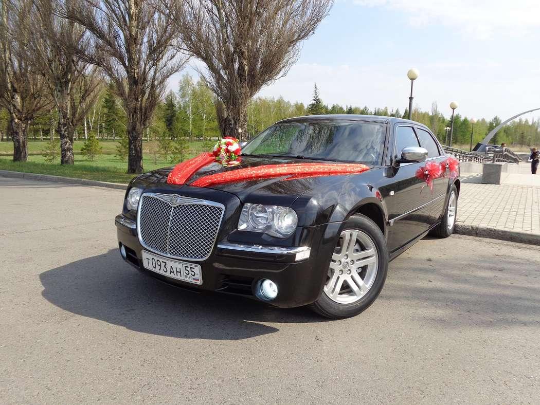 Черный автомобиль, украшенный красными широкими лентами ткани с блестками, на зеркале и ручках дверей небольшие красные букетики. - фото 2364844 КРАЙСЛЕР 300С