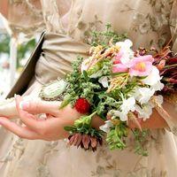 Невеста в свело-белом платье с букетом невесты из фиалок в руках