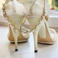 Молочно-белые открытые туфли на высоких каблуках для невесты и колье из позолоченного металла, кристаллов и жемчуга.