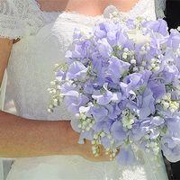 Невеста в белом кружевном платье с букетом из белых ландышей и светло-сиреневых латирусов