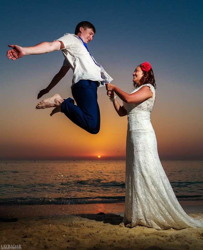 На пляже стоит невеста и держит жениха за галстук, она в белом, длинном платье, он подпрыгнул вверх в белой рубашке и голубых - фото 2715897 Фотограф в Дубае Александр Лаврадар