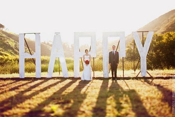 Жених и невеста стоят на фоне огромных белых букв - фото 2763111 Добрый Фей - организация свадьбы
