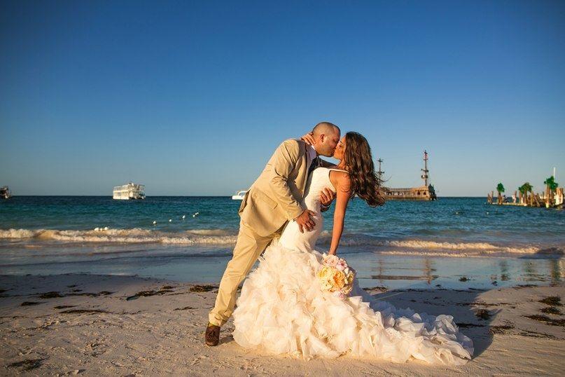 В лучах заката, стоя на берегу, парень в горчичном костюме, обняв за талию, целует невесту в белоснежном открытом платье с - фото 2842071 Destiny dress - show room, свадебные платья