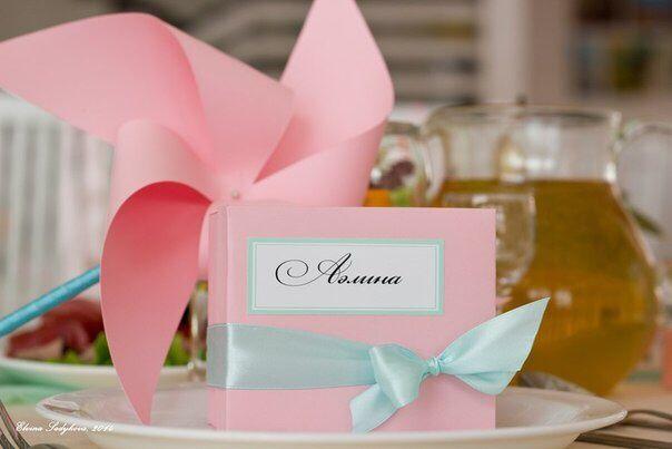 Розовая бонбоньерка с именем гостя в голубой ленточке на фоне розовой вертушки. - фото 2839125 Студия декора Rizi