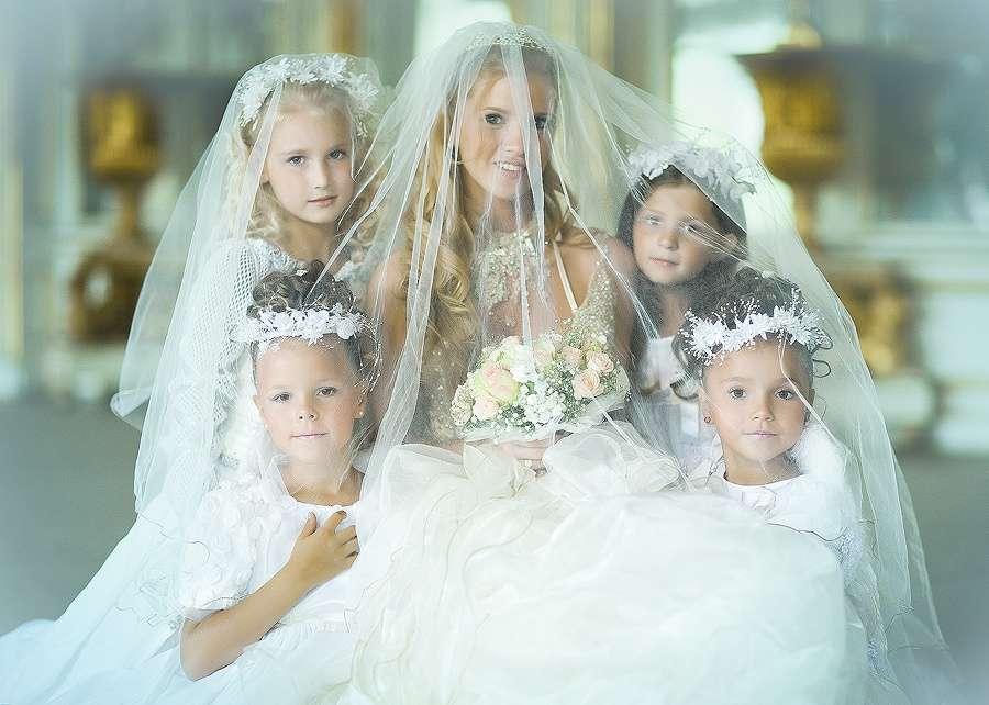 """Девочки возле невесты одеты в белые платья в одном стиле с изящными белыми веночками на голове, стоят накрыты фатой невесты - фото 3178411 Свадебный салон """"Golden-Story"""""""
