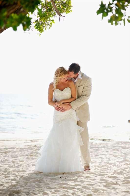 """На пляже на фоне океана жених в светлом костюме обнимает за талию и целует невесту в открытом белом платье """"русалка"""" - фото 3380215 Holiday Vibes Photo фотосессии в Мексике"""