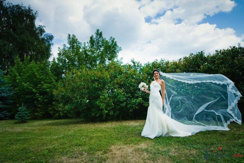 Невеста в белом длинном платье стоит на фоне зеленых деревьев - фото 49447 Свадебные аксессуары by Оксана Karamelnaya