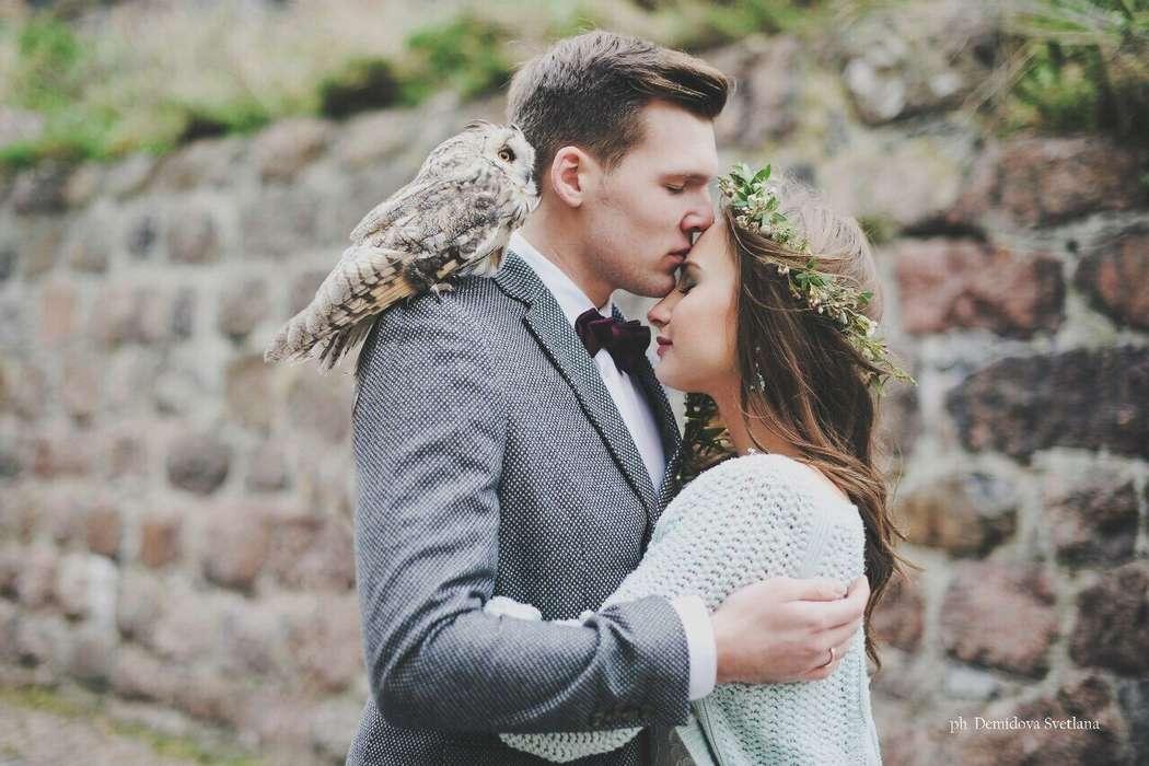 Жених с совой на плече и невеста, прислонившись друг к другу, стоят на фоне каменной стены - фото 3618827 Оформление свадеб MagicDecoStyle
