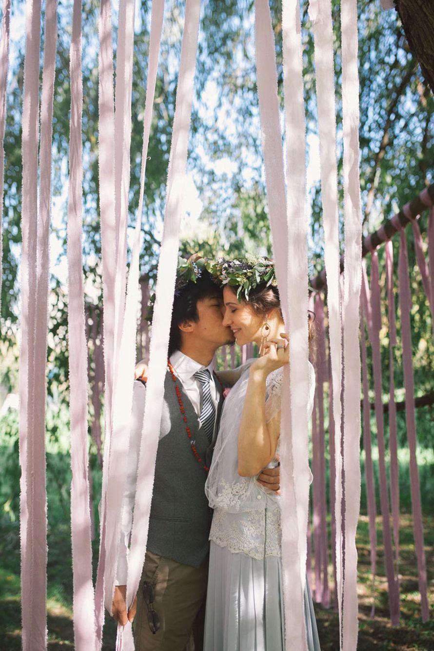 Жених и невеста стоят, прислонившись друг к другу, посреди деревьев, украшенных розовыми лентами - фото 3671857 Regil sisters - цветы и декор
