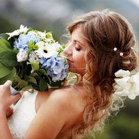 Невеста с белым цветком в волосах и свадебный букет невесты