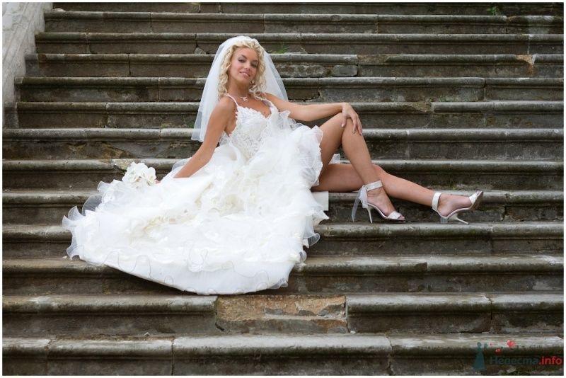 Невеста в белом длинном платье сидит на лестнице