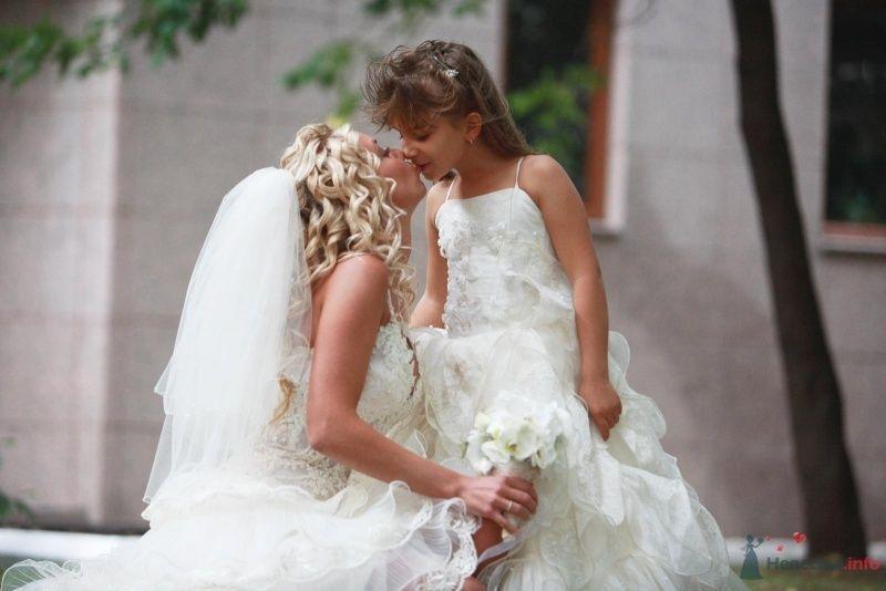 Девочка в длинном пышном платье целует невесту