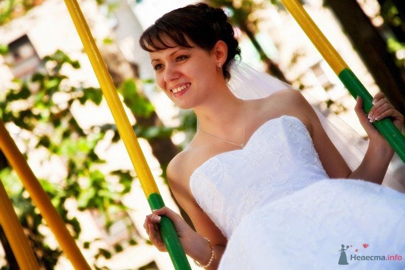 Невеста в белом длинном платье сидит на качелях